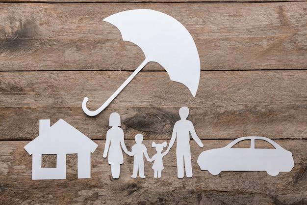 Papierschattenbild der familie, des regenschirms, des hauses und des autos auf hölzerner oberfläche. lebensversicherungskonzept