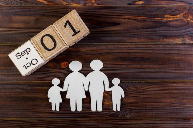 Papierschattenbild der familie mit dem 1. september auf einem dekorativen kalender auf hölzernem.