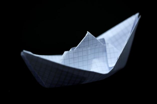 Papierschiff auf schwarzem hintergrund