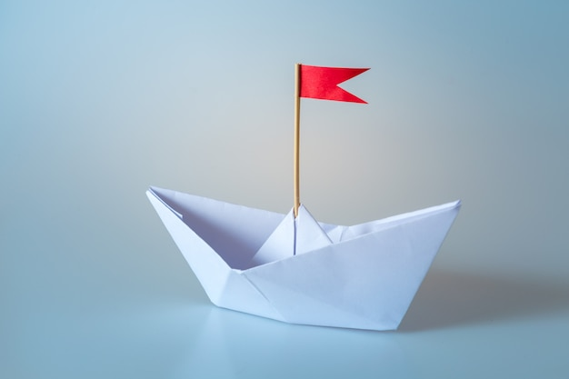 Papierschiff mit roter fahne auf blau