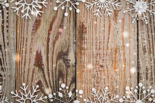 Papierschneeflocken auf hölzernem hintergrund
