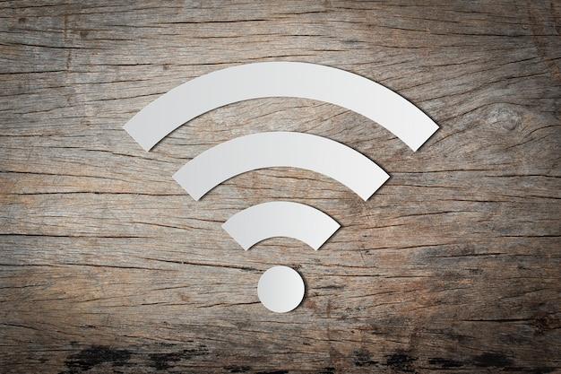 Papierschnitt der freien wifi-ikone auf hölzernem hintergrund