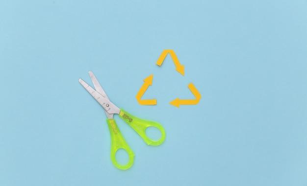 Papierschnitt recycelte pfeile unterzeichnen auf blauem pastellhintergrund mit einer schere.