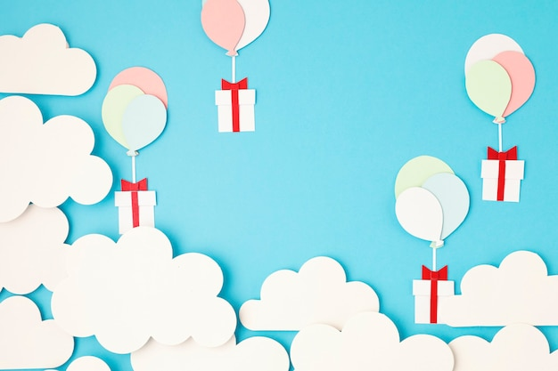 Papierschnittballons und geschenkbox, die im blauen himmel mit wolken schweben