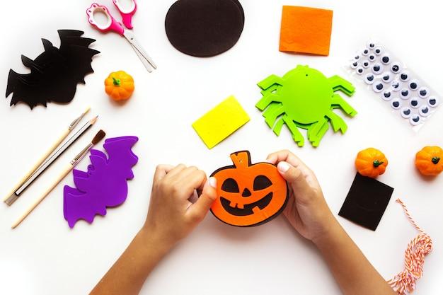 Papierschnitte für halloween. handgeschnittenes papier. kürbisse, fledermäuse und spinnen schere und kleber. auf hellem hintergrund. ansicht von oben. flach liegen. heimwerken. schritt für schritt