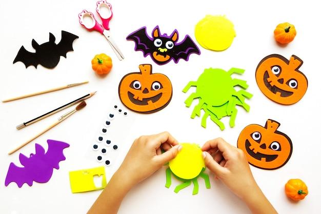 Papierschnitte für halloween. handgeschnittenes papier. kürbisse. schere und kleber. auf hellem hintergrund. ansicht von oben. flach liegen. heimwerken. schritt für schritt