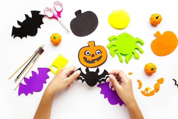 Papierschnitte für halloween. handgeschnittenes papier. kürbisse. schere und kleber. auf hellem hintergrund. ansicht von oben. flach liegen.
