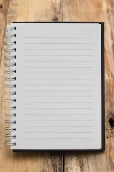 Papierseitennotizbuch auf einer hölzernen tabelle