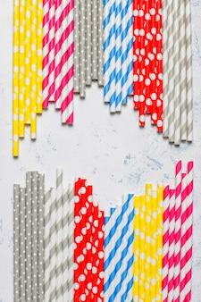 Papierstrohhalme in verschiedenen farben auf hellem tisch mit