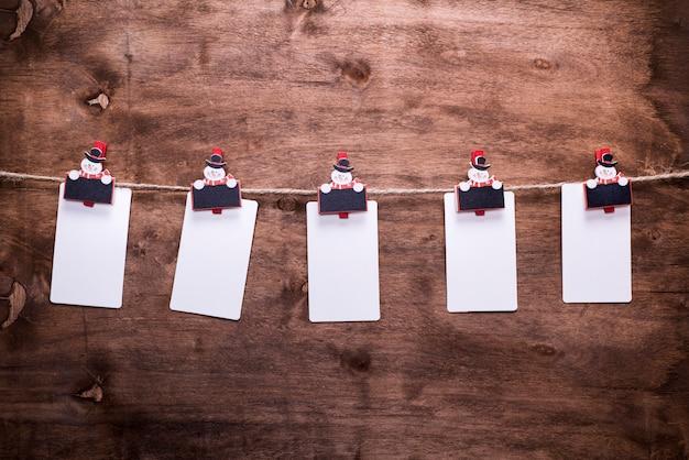 Papiertags, die an einem seil hängen, hingen an den dekorativen weihnachtswäscheklammern