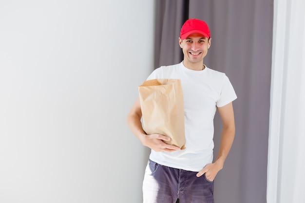 Papiertasche und lebensmittelbehälter in den händen eines lächelnden lieferboten. qualitätsservice eines restaurants.