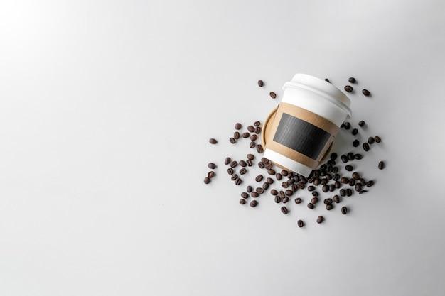 Papiertasse kaffee und bohnen auf weißem tabellenhintergrund. ansicht von oben. platz für text