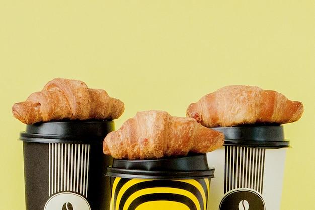 Papiertasse kaffee und hörnchen auf gelb