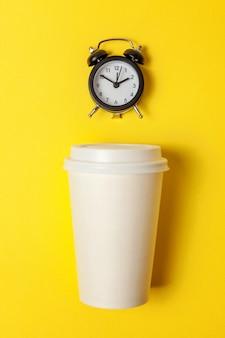 Papiertasse kaffee und wecker auf gelbem hintergrund