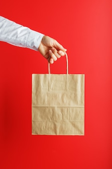 Papiertüte auf armeslänge, braune basteltasche zum mitnehmen lokalisiert auf rotem hintergrund. layout der verpackungsvorlage mit platz zum kopieren, für werbung. das konzept der leistungserbringung.