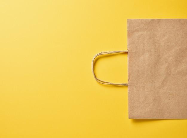 Papiertüte auf gelbem hintergrund, ansicht von oben