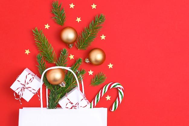 Papiertüte auf rotem hintergrund mit geschenkbox kugeln weihnachtsbaum weihnachtsgeschenk vorbereitung konzept