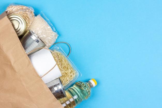 Papiertüte mit einer krisennahrungsmittelversorgung für den zeitraum der quarantäneisolierung auf einem blauen hintergrund