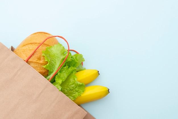 Papiertüte mit essen: grüne blätter von salat, brot und banane. auf blauem hintergrund, draufsicht auslegen