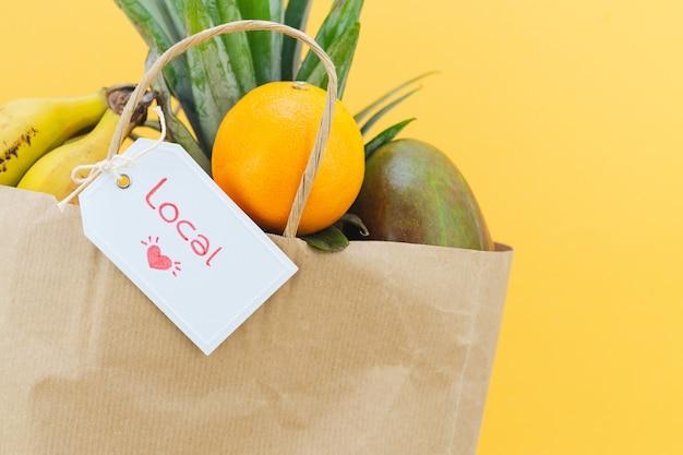 Papiertüte mit etikett mit wort local mit verschiedenen früchten auf gelbem hintergrund.