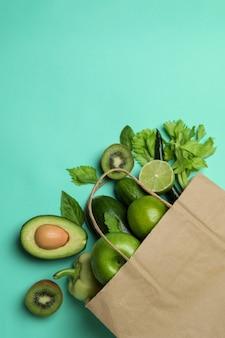 Papiertüte mit grünem gemüse auf minzhintergrund