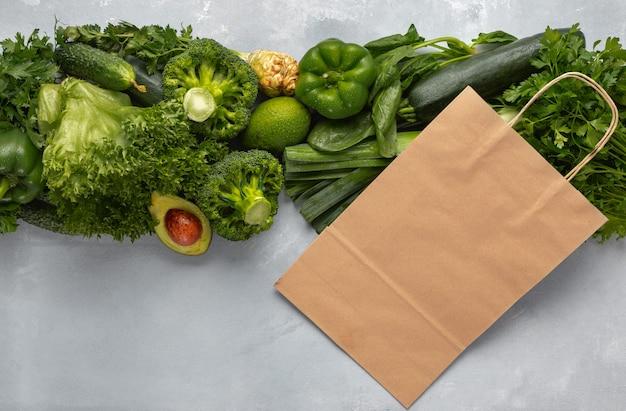 Papiertüte mit grünem gemüse. kaufen sie gesundes veganes und vegetarisches essen
