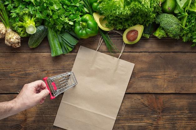 Papiertüte mit grünem gemüse und kleinem einkaufswagen. kaufen sie gesundes veganes und vegetarisches essen