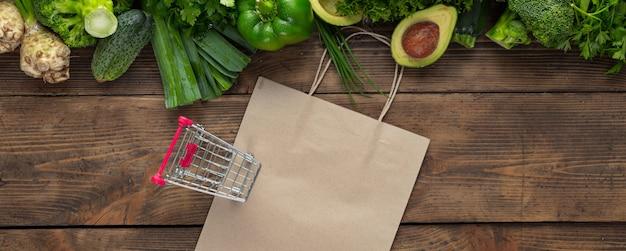 Papiertüte mit grünem gemüse und kleinem einkaufswagen