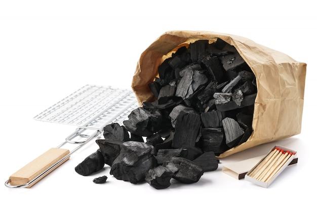 Papiertüte mit holzkohle, grill, streichhölzern. grillvorbereitungsset.
