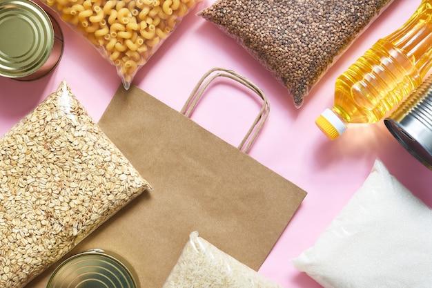 Papiertüte mit lebensmittel liefert krisenlebensmittelbestand für quarantäne. nudeln, buchweizen, zucker, reis, müsli, konserven. spende. draufsicht