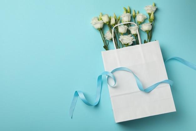 Papiertüte mit rosen und band auf blauem hintergrund