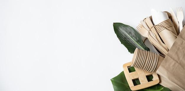 Papiertüte mit umweltfreundlichem einweggeschirr, tellern und gläsern von oben.