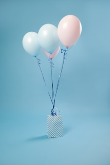 Papiertüte mit weiß-blauen streifen und farbigen rosa-blauen luftballons