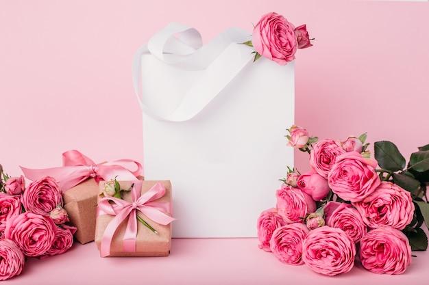 Papiertüte und geschenkboxen isoliert auf rosa