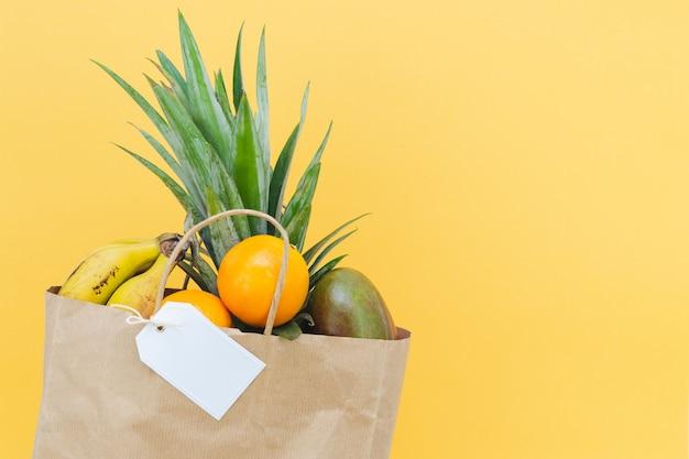 Papiertüte und kartonetikett ohne beschriftung mit verschiedenen früchten auf gelbem hintergrund. attrappe, lehrmodell, simulation.