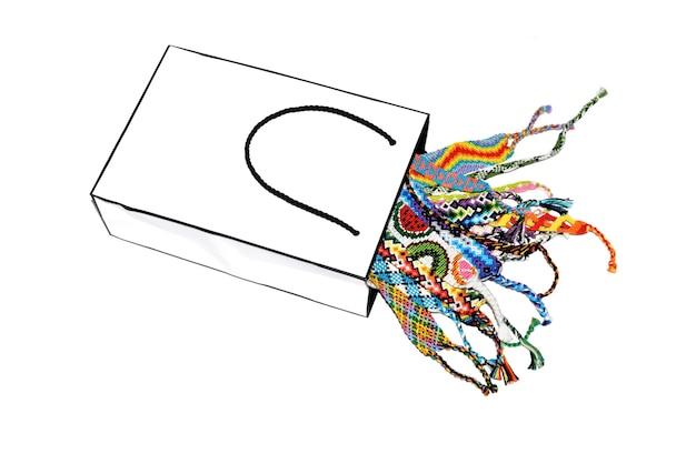 Papiertüte voll von diy-freundschaftsbändern auf einem weißen hintergrund