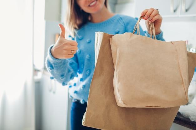Papiertüte wahl. frau, die eco paket anstelle des polyethylens wählt und zu hause daumen oben auf küche zeigt