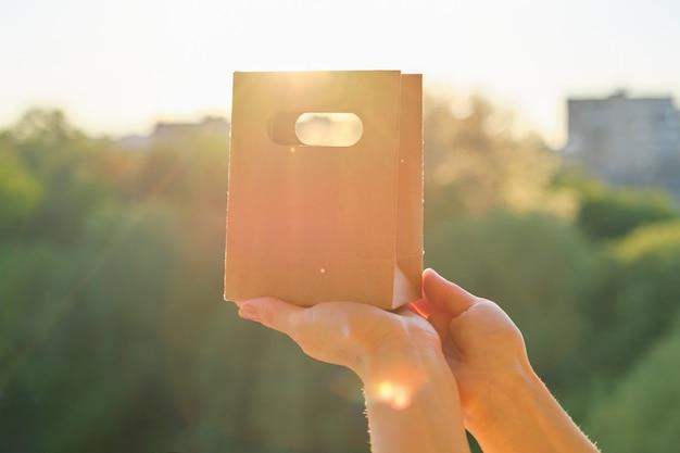Papiertüte zum einkaufen in der hand der frau, hintergrundsonnenuntergang