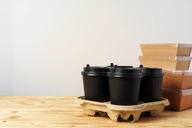 Papiertüten mit behältern zum mitnehmen von lebensmitteln und kaffeetassen. brotdose