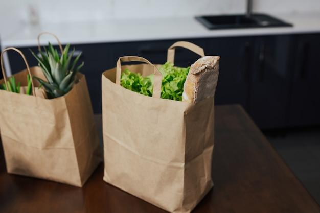 Papiertüten mit frischem gemüse und obst auf holztisch in der küche