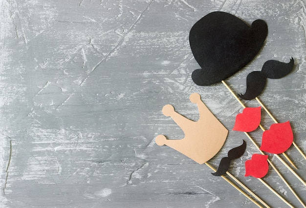 Papierzubehör auf einem stock für ein fotoshooting an feiertagen oder auf partys. konkreter hintergrund.