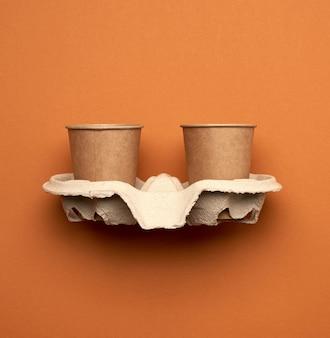Pappbecher aus braunem bastelpapier und recyclingpapierhaltern