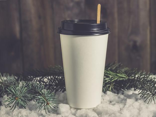 Pappbecher kaffee im schnee mit tannenzweigen