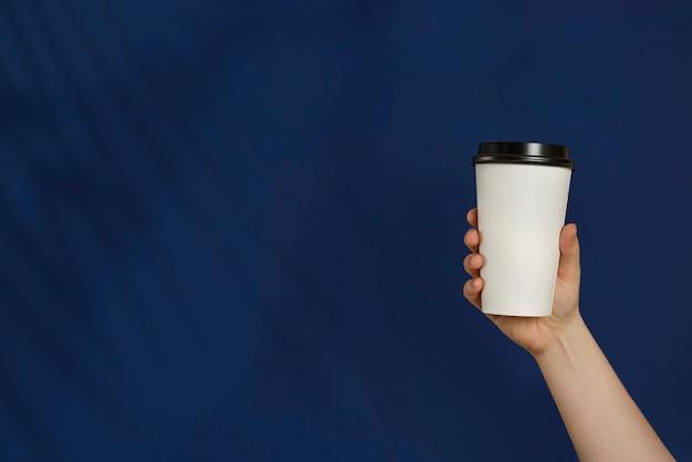 Pappbecher kaffee oder tee auf einem klassischen blauen hintergrund. modell der männlichen hand, die pappbecher lokalisiert hält. wegbringen. werbung für kaffee. fügen sie ihren text hinzu.
