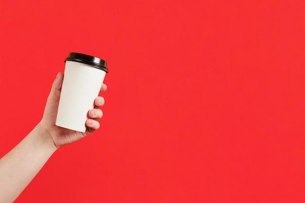 Pappbecher kaffee oder tee auf rotem grund. modell der männlichen hand, die pappbecher lokalisiert hält. wegbringen. werbung für kaffee. fügen sie ihren text hinzu.