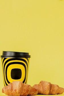 Pappbecher kaffee und croissants auf gelbem hintergrund, kopierraum