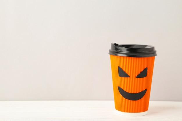 Pappbecher mit halloween-gesicht im grauen hintergrund. draufsicht