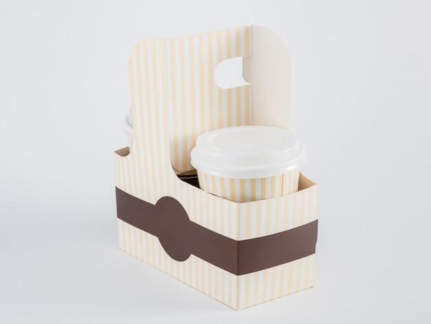 Pappbecher mit kaffee in einer takeaway-box auf weißem hintergrund