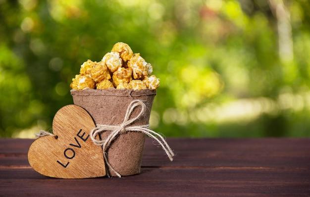 Pappbecher mit karamellisiertem popcorn und holzherz