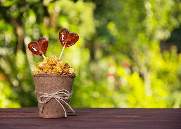 Pappbecher mit karamellpopcorn und süßigkeiten
